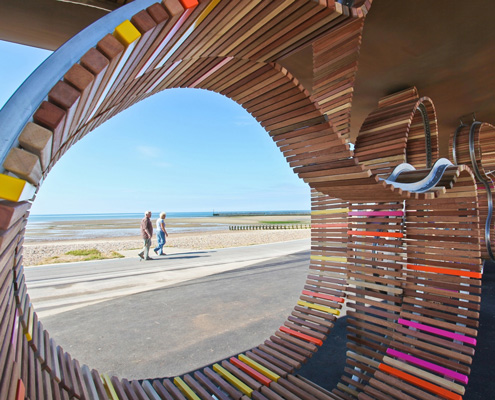 an view of littlehampton beach looking through part of the longest bench in the uk
