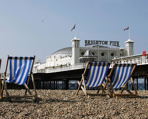 a view of deckchairs, with brighton pier in the background